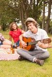Счастливые друзья в парке имея пикник Стоковая Фотография