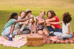 Счастливые друзья в парке имея пикник Стоковое Изображение