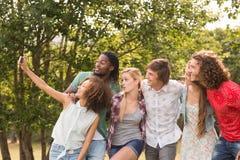 Счастливые друзья в парке принимая selfie Стоковая Фотография