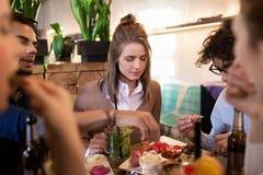 Счастливые друзья есть и выпивая на баре или кафе Стоковая Фотография
