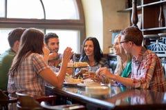 Счастливые друзья есть и выпивая на баре или пабе Стоковая Фотография RF