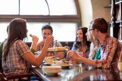Счастливые друзья есть и выпивая на баре или пабе Стоковое фото RF