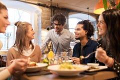 Счастливые друзья есть и выпивая на ресторане Стоковое фото RF