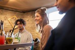 Счастливые друзья есть и выпивая на ресторане Стоковое Изображение RF