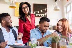 Счастливые друзья есть на ресторане Стоковое фото RF