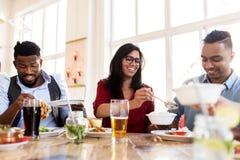 Счастливые друзья есть на ресторане Стоковые Фото