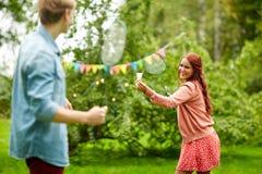 Счастливые друзья играя бадминтон на саде лета Стоковые Изображения RF