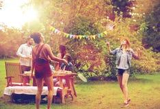 Счастливые друзья играя бадминтон на саде лета Стоковая Фотография