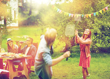 Счастливые друзья играя бадминтон на саде лета Стоковая Фотография RF