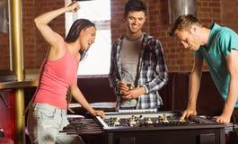 Счастливые друзья играя футбол таблицы Стоковая Фотография