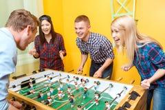 Счастливые друзья играя хоккей таблицы Стоковое Фото