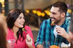 Счастливые друзья имея обедающий на ресторане Стоковые Изображения
