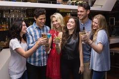 Счастливые друзья имея питье совместно Стоковое фото RF