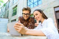Счастливые друзья используя современную технологию Стоковое Изображение RF
