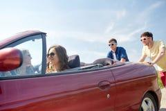 Счастливые друзья нажимая сломанный автомобиль cabriolet Стоковые Изображения