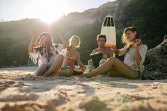 Счастливые друзья наслаждаясь каникулами на пляже Стоковые Фотографии RF