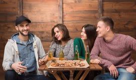 Счастливые друзья отдыхая в пиццерии Стоковая Фотография