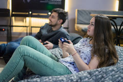 Счастливые друзья пар играя видеоигры при кнюппель сидя на стуле сумки фасоли Стоковое Фото