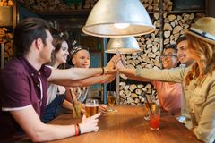 Счастливые друзья при пить делая максимум 5 на баре стоковое фото