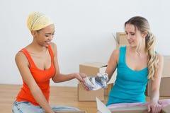 Счастливые друзья развертывая коробки в новом доме Стоковая Фотография RF