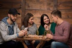 Счастливые друзья связывая пока один человек смотря его мобильный телефон Стоковое фото RF
