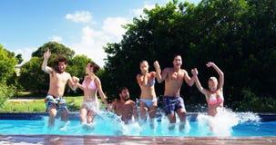 Счастливые друзья скача в бассейн сток-видео