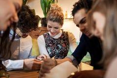 Счастливые друзья смотря к меню на ресторане Стоковое Изображение RF