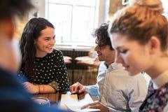 Счастливые друзья смотря к меню на ресторане Стоковая Фотография RF
