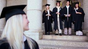 Счастливые друзья стоя за белокурым студентом сток-видео