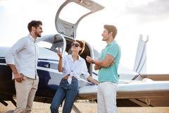 Счастливые друзья стоя и говоря около малого самолета Стоковые Фотографии RF