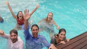 Счастливые друзья с одеждами в бассейне видеоматериал