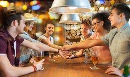 Счастливые друзья с пить и руки на верхней части на баре стоковое фото rf