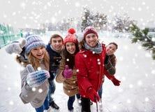 Счастливые друзья с smartphone на катке катания на коньках Стоковое Изображение