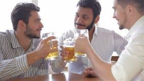 Счастливые друзья улавливая вверх над пинтами в баре сток-видео