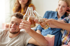 Счастливые друзья clinking партия пивных бутылок дома Стоковое Фото