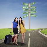Счастливые 2 друз женщины с чемоданами Стоковое фото RF
