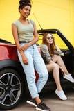 Счастливые 2 друз молодых женщин стоя близко автомобиль Стоковое Изображение RF