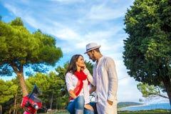Счастливые свободные пары свободы управляя самокатом возбужденным на летних отпусках отдыхают стоковая фотография