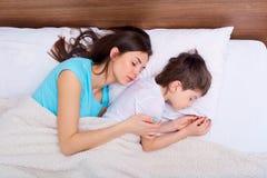 Счастливые семья, мать, и сын отдыхая на белой кровати спать Стоковые Изображения