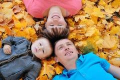Счастливые семья, мать, отец и сын лежа на листьях осени Стоковое Изображение