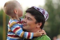 Счастливые семья, сын и отец тратя время совместно внешнее Стоковые Изображения RF