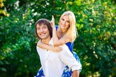 Молодые пары имея потеху piggybacking в парке стоковая фотография rf