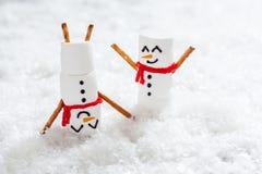 Счастливые смешные snowmans зефира на снеге Стоковая Фотография