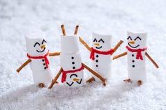 Счастливые смешные snowmans зефира на снеге Стоковое Изображение