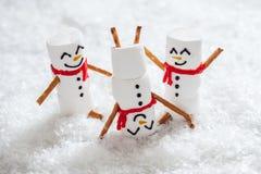 Счастливые смешные snowmans зефира на снеге Стоковое Фото