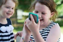 Счастливые смеясь над дети играя с Smartphone снаружи стоковые изображения