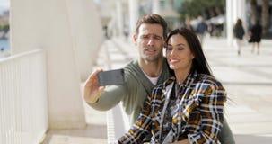 Счастливые смеясь над пары принимая их selfie видеоматериал
