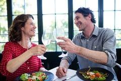 Счастливые средн-постаретые пары провозглашать каннелюры шампанского пока имеющ обед Стоковые Изображения