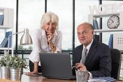 Счастливые старейшины в офисе стоковые фото