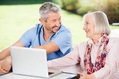 Счастливые старшие женщина и смотритель с компьтер-книжкой дальше Стоковые Фото